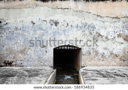 A storm water tunnel mouth with teeth on a blank weathered concrete wall.  - stock photo