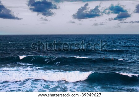 A stormy ocean a dusk with large waves and two surfers in the distance - stock photo