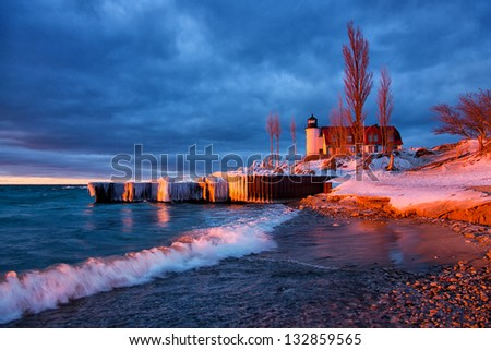 A stormy sky creates a dramatic scene at Point Betsie Lighthouse along the Lake Michigan shoreline. A setting sun scatters evening light on the waters surface, lighthouse and waves. - stock photo