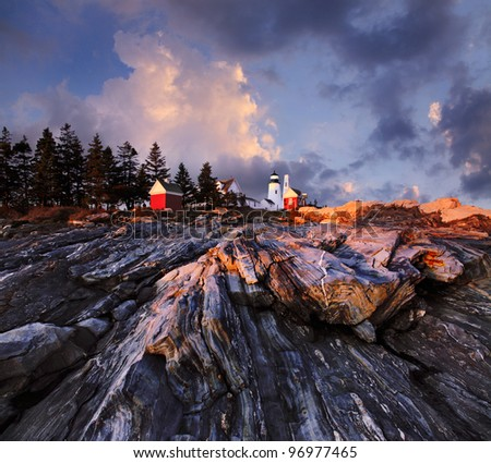 A Stormy Sunset Casts Dramatic Light Over The Rugged Sea Coast At The Foot Of The Pemaquid Point Lighthouse, Bristol Maine, USA - stock photo