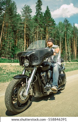 A story of love and offer bikers on the bike a Sunny day on the road. Brutal man, brown hair, a beard Moto