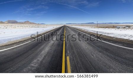 a straight open section of highway 6 road in Nevada stretches on to the distant horizon in the winter - stock photo