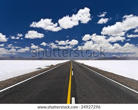 A straight road across an open salt mine. - stock photo