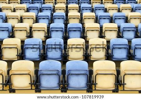 A straight view of empty bleachers, Yellow and blue baseball stadium seats - stock photo