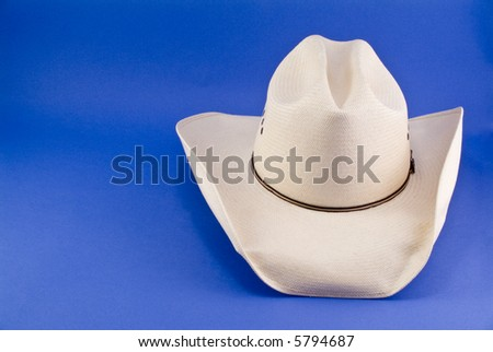 A straw cowboy hat taken on a blue background. - stock photo