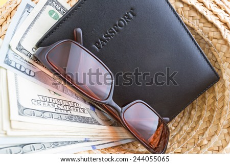A straw hat with a leather passport holder, sunglasses and vacation cash. - stock photo