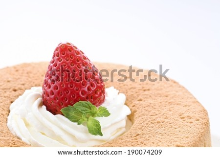 A strawberry in cream on top of a cake. - stock photo