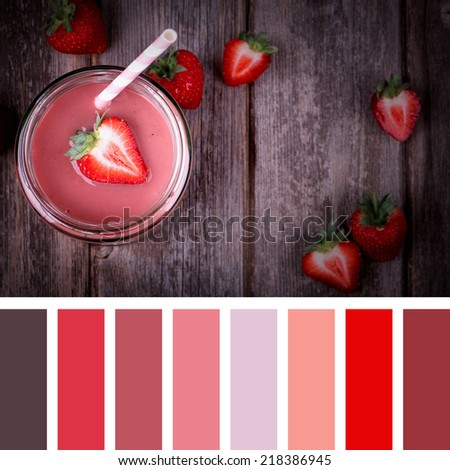 A strawberry smoothie in a jar with straw, vintage style over old wood background, in a colour palette with complimentary colour swatches. - stock photo