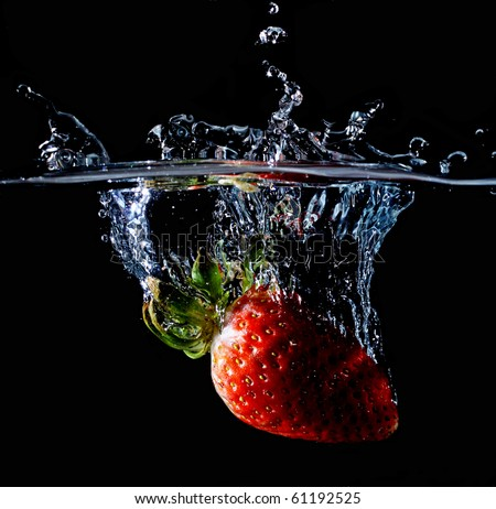 A strawberry splashing into water - stock photo