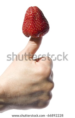 a strawberry stuck in a thumb - stock photo