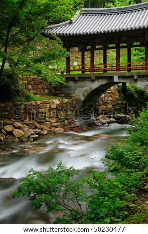 A stream flowing beneath a bridge built using traditional Korean Buddhist architecture - Extended exposure. - stock photo
