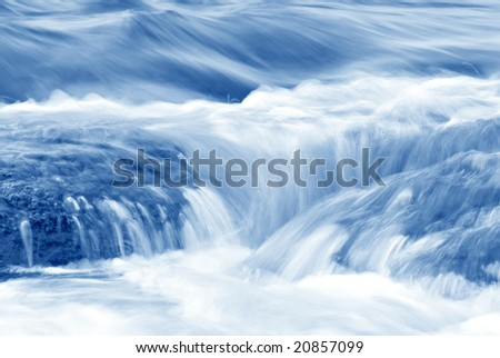 A stream flowing over rocks in shades of blue. - stock photo