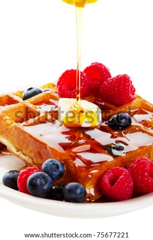 A stream of golden Canadian maple syrup adds the finishing touch to a delicious breakfast of belgian waffles with fresh raspberries and blueberries.  Shot on white background. - stock photo