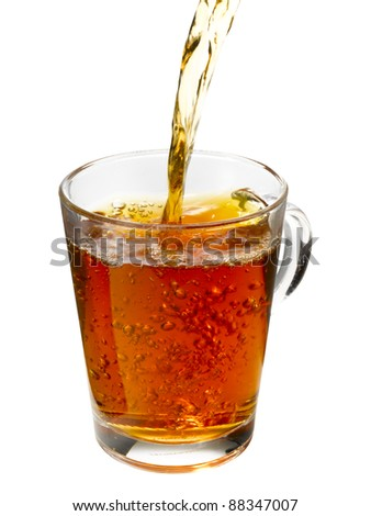 A stream of tea falling in a cup. The cup is filled with tea and bubbles. - stock photo