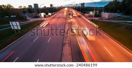 A stream of traffic as cars and trucks traverse the inter provincial bridge at dusk. - stock photo