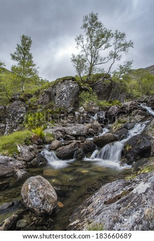 A stream with small waterfall during a weather change near Fort William and Glenn Nevis. - stock photo