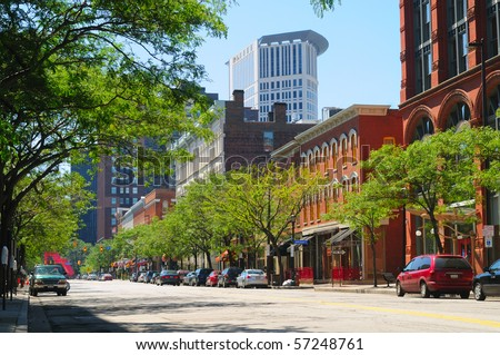 A street in downtown Cleveland Ohio's trendy Warehouse District, with the Justice Center rising behind - stock photo