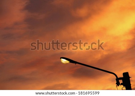a street lamp against the sun-setting background - stock photo