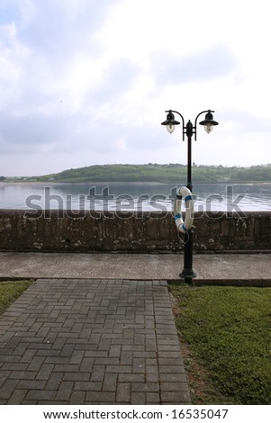 a street lamp and buoy on a pier in youghal co cork ireland - stock photo