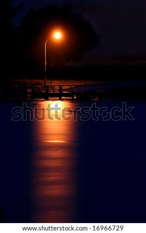 A street light reflecting over the ocean at night - stock photo