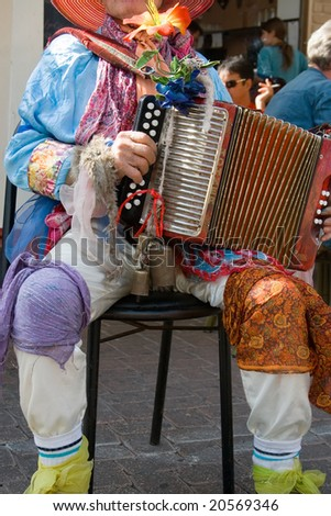 A street musician in colorful costume playing accordion. Tel-Aviv, Israel.