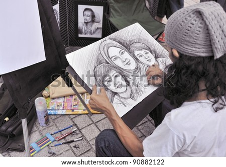 A street painter sketching a family portrait - stock photo