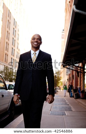 A street portrait of a business man walking down the sidewalk