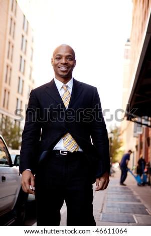 A street portrait of a business man walking on a sidewalk - stock photo