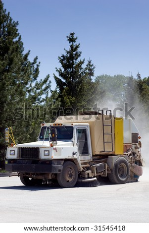A street sweeper truck with a dust cloud behind. - stock photo