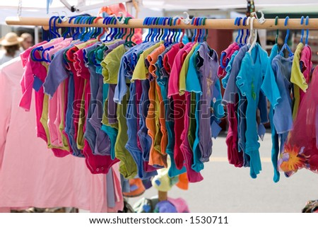 A street vendor shows off a colorful rainbow like collection of baby clothes.