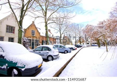 a street with houses and cars are covered with snow in wintertime