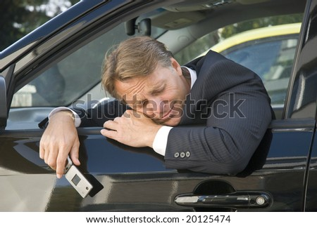A stressed and tired businessman holds his cellphone while sitting in his car - stock photo