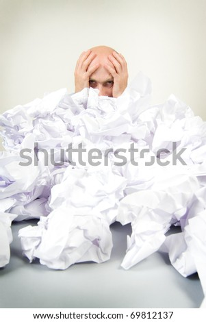 A stressed man holding his head. - stock photo