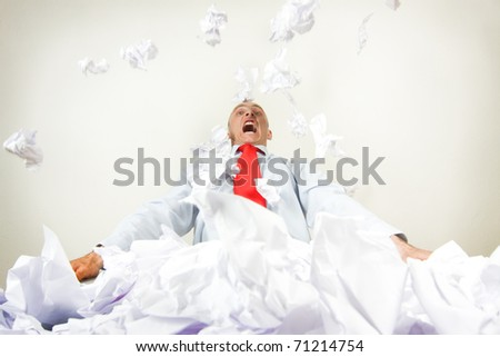 A stressed out businessman being buried by papers. - stock photo