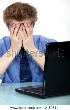 A stressed out man in front of his laptop - stock photo