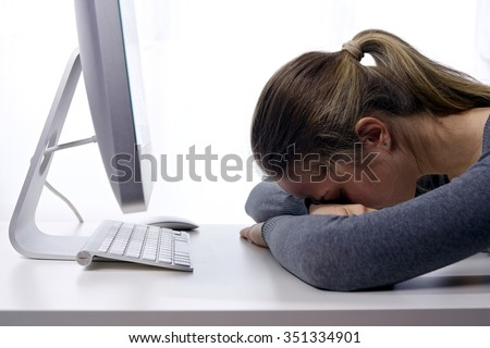A stressed young girl sleeping in front of her computer/Stress at Workplace. Sleepy Student - stock photo