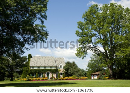 A striking English Manor style house surrounded by beautiful gardens and huge oaks is surprisingly located in western New York! - stock photo