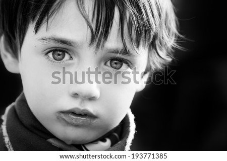 A striking young boy looking into camera - stock photo