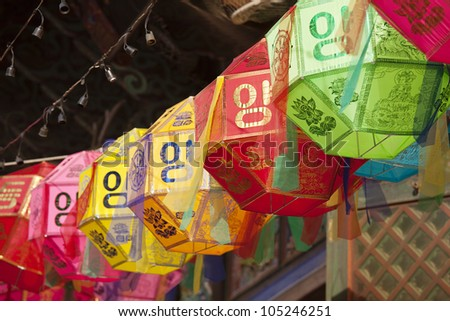 A string of colored paper lanterns hang over the outside entrance to the Buddhist temple of Bongeunsa in Seoul, South Korea. - stock photo