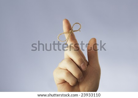 A string tied around an index finger - stock photo