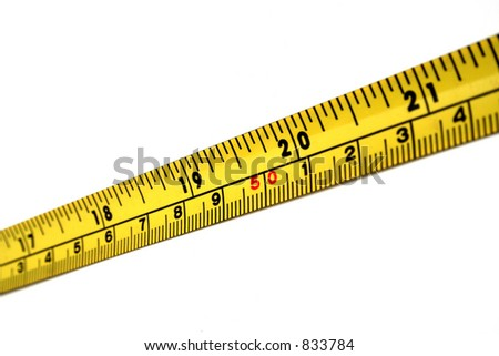 A strip of yellow and black measuring tape. - stock photo