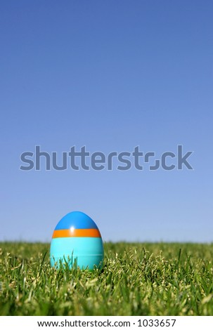 A striped plastic Easter egg on the grass with a blue sky - shallow DOF. - stock photo