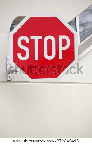 A strong colored stop sign on the facade of a building / Stop sign - stock photo