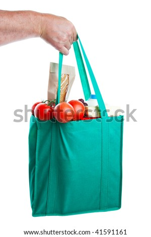 A strong hand holding an environmentally friendly bag full of groceries.  Shot on white background.