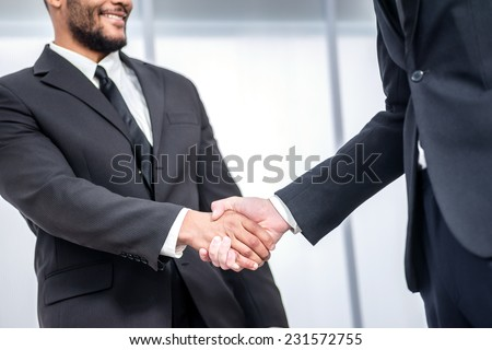 A strong handshake. Two Confident businessman firmly shake hands with each other while two colleagues talking in the background - stock photo