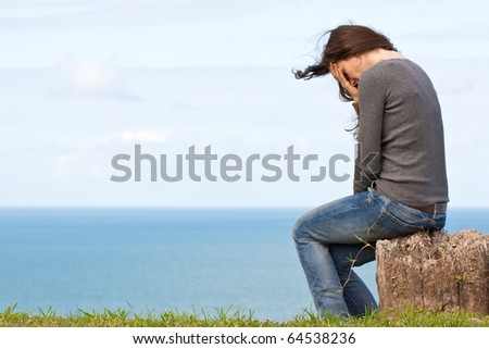 A strong image of a depressed and upset young woman sitting outside with her head in her hands