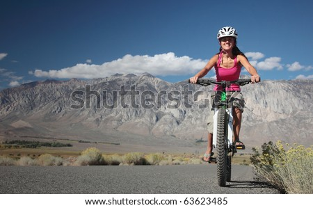 A strong woman rides along the road in the Sierra Nevavda of California. - stock photo