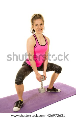 a strong woman with a smile, doing a squat with a weight in her hands. - stock photo