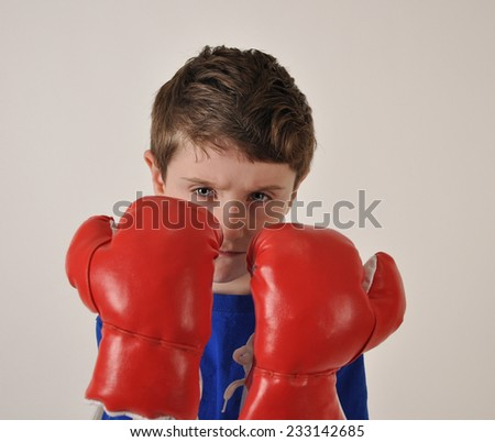 A strong young boy is wearing red boxing gloves on a white background and looks tough for a fitness or athlete concept. - stock photo