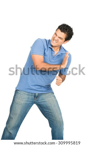 A struggling latino man casual clothes driving back, defending, forcing, pushing against imaginary insert object coming from side using body weight - stock photo